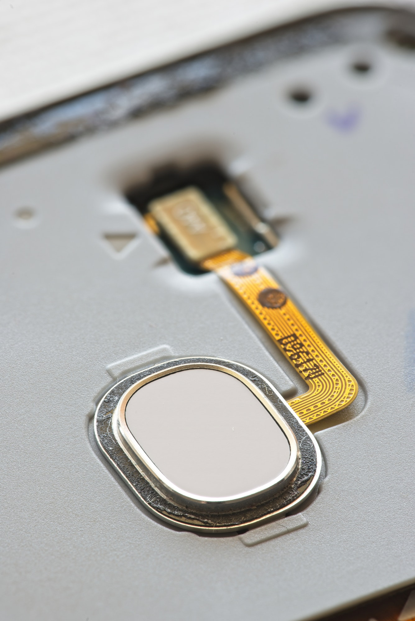 Macro detail of fingerprint scanner on smartphone with exposed electronic wires.
